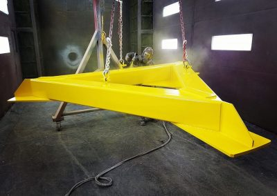 Large weldment blasted and painted in safety yellow